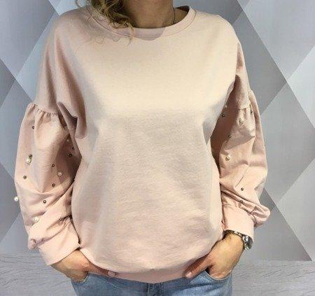 Bluza różowa z perłami na rękawach.